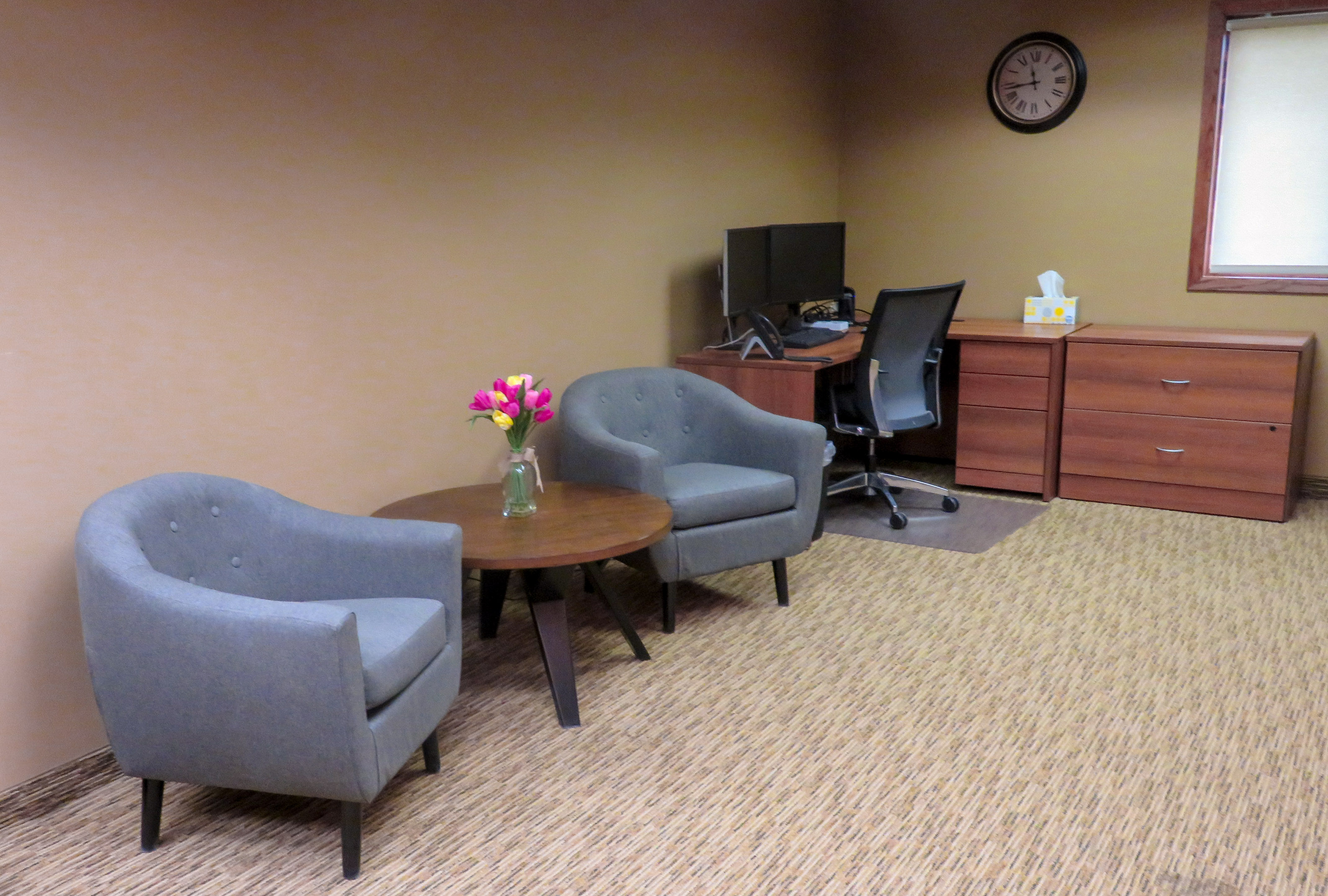 Another photo of the visitor space from another angle. It shows the area behind the reception desk with two chairs and a desk with a computer.