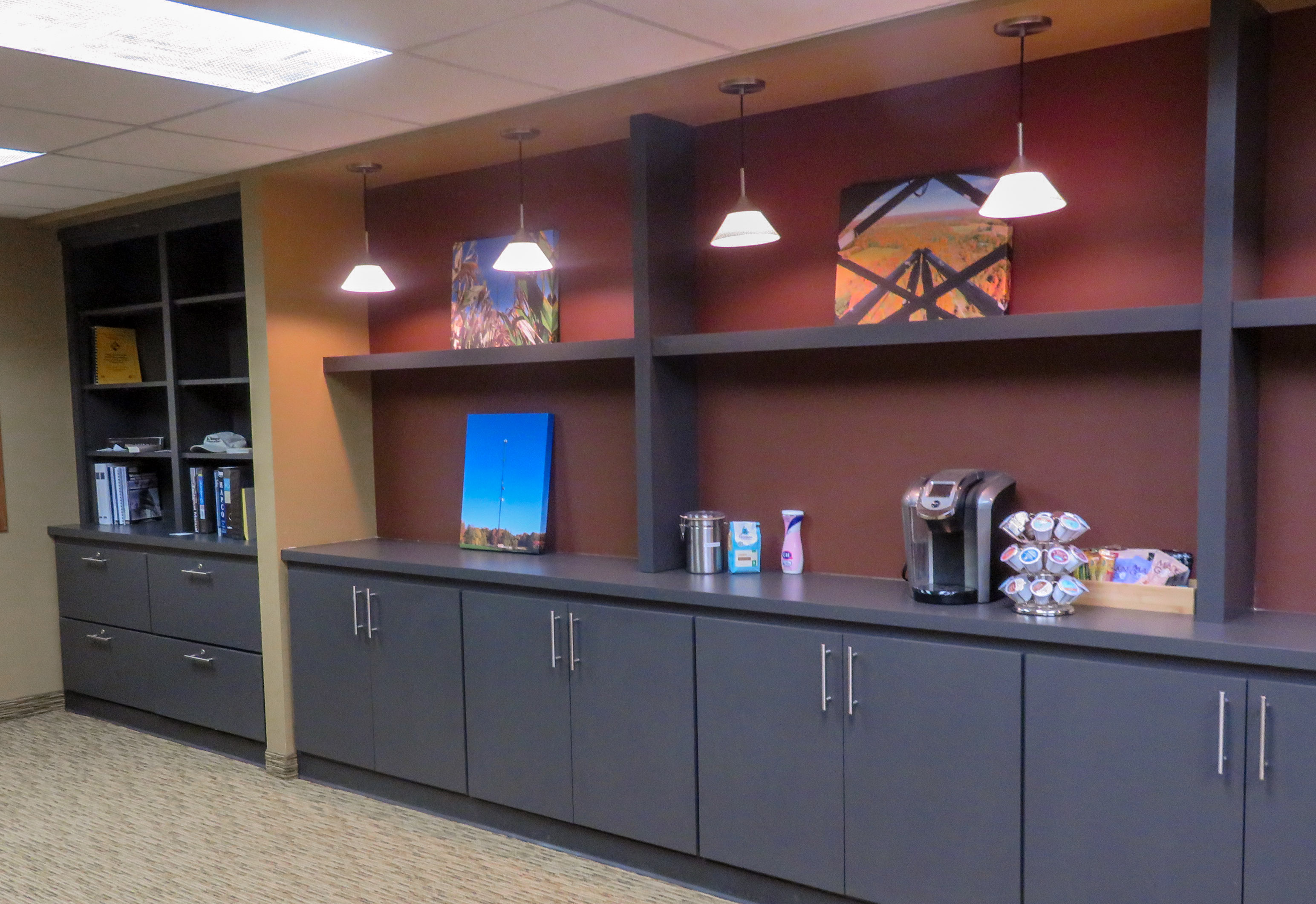 The last photo of the visitor area, which shows a wall with cabinets on the bottom, a coffee station on top of the cabinets, and items on the wall.
