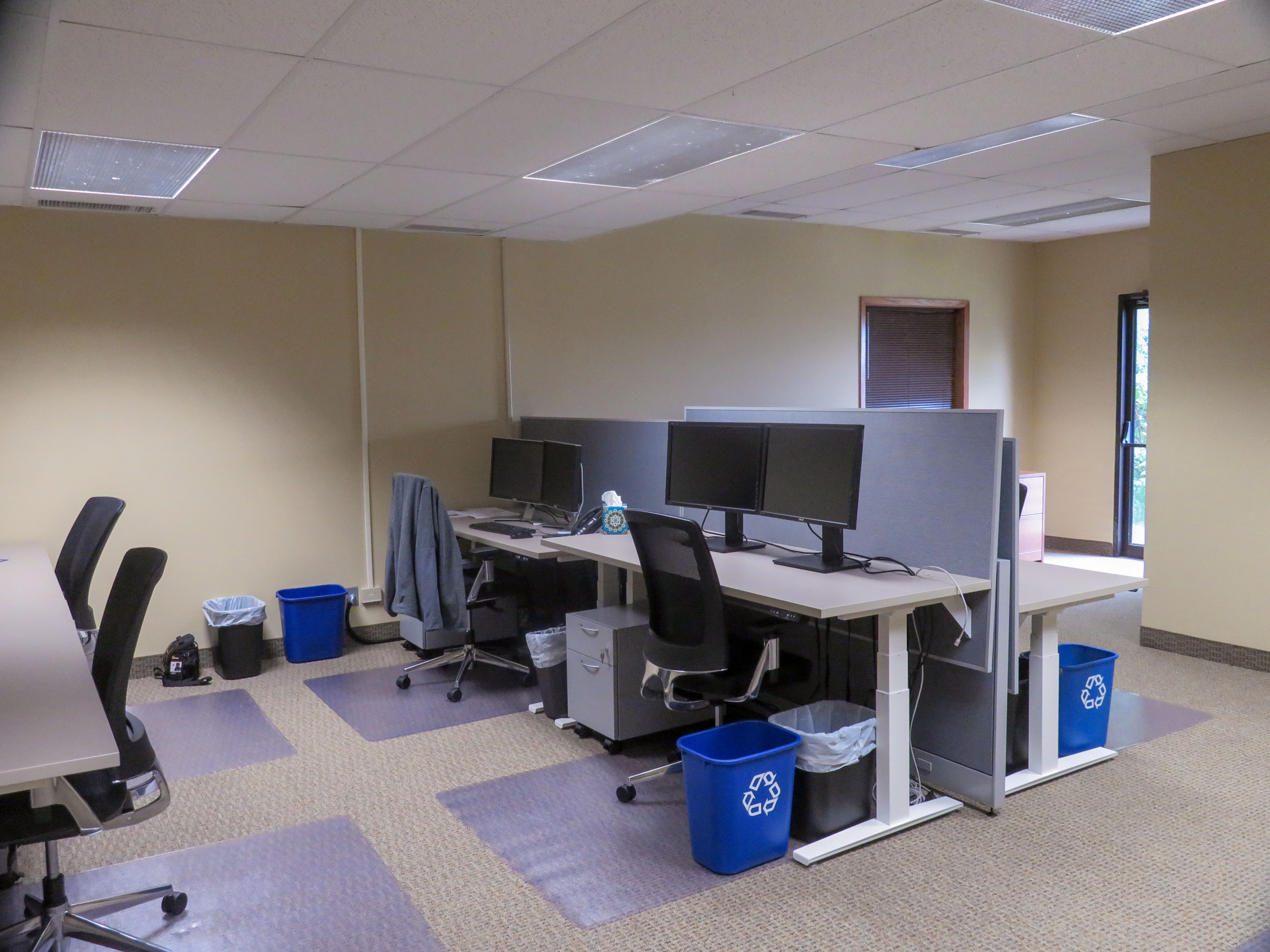 Photo showing employee work-space featuring adjustable desks.