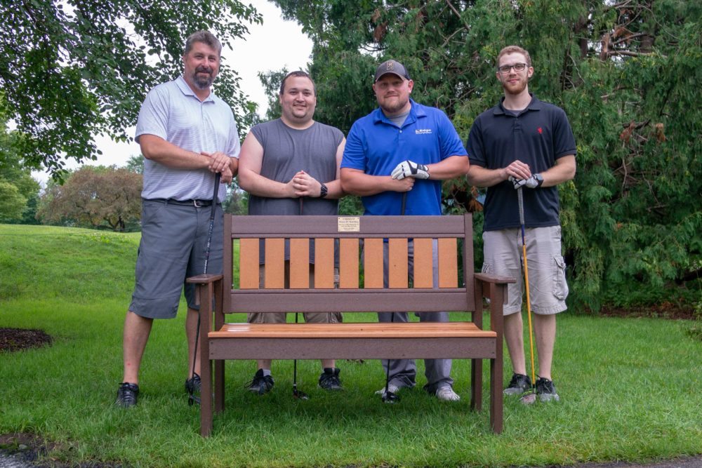 Four Edge Employees pose behind a bench in memory of a deceased employee.